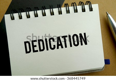 Dedication memo written on a notebook with pen - stock photo