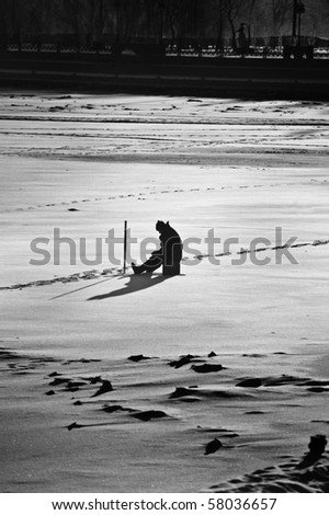 Dedication/patience concept - lone man waiting on fish on the Dnipro River in Kyiv, Ukraine - stock photo