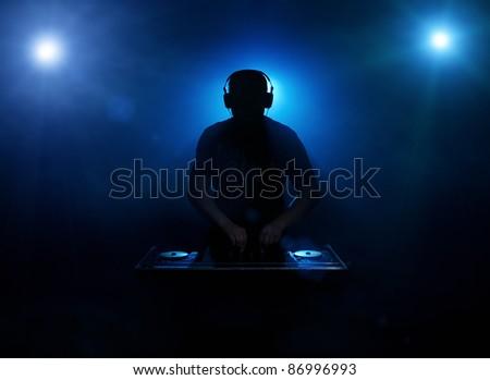 Dee jay silhouette back lit - stock photo