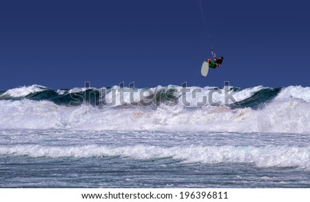 DEE WHY, AUSTRALIA - JANUARY 25 2014: A kite surfer goes airborne in stormy seas. - stock photo