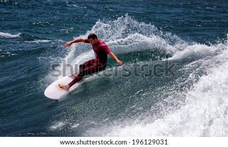 DEE WHY, AUSTRALIA - JANUARY 25,2014: An accomplished surfer cuts through a large wave in heavy surf. - stock photo