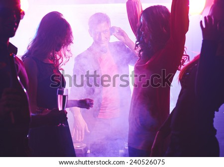 Deejay looking at dancing girl at party - stock photo
