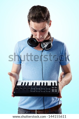 Deejay with headphones holding midi keyboard in hands while being surprised.Gradient blue background. - stock photo