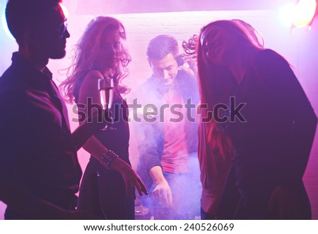 Deejay working and cool girls dancing in nightclub - stock photo