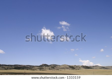 Deep blue sky and white clouds on the plains between Colorado and Wyoming.  Suitable for backgrounds.  High resolution. - stock photo