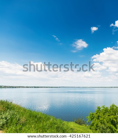 deep blue sky with clouds over river and green grass - stock photo