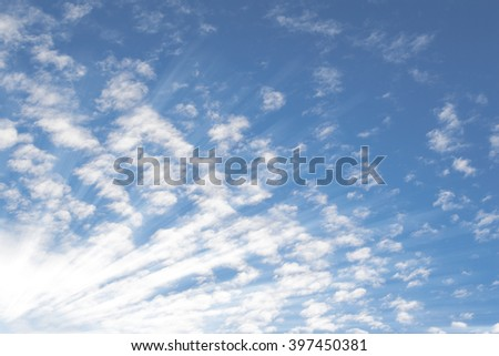 Deep blue summer sky with small Altocumulus clouds and bright sunrays sunbeams - stock photo