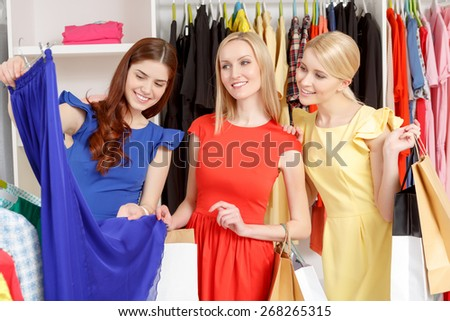 Deep blue. Three female shoppers holding paper bags and looking at a dark blue skirt with clothing rack on a background - stock photo