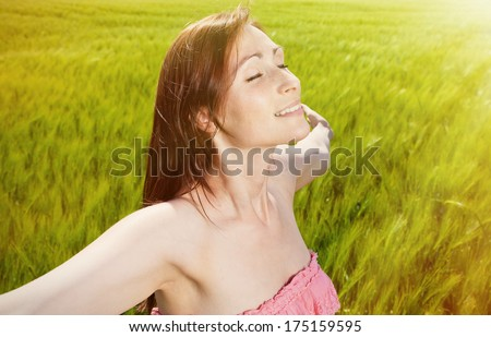deep breathing ypunger female on sunny day - stock photo