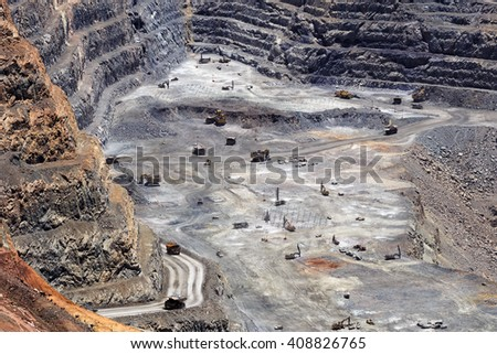 Deep down in the super pit gold mine of Kalgoorlie in Western Australia. Big excavators, trucks and other machinery seem small in a distance at hard heavy industry work as seen from the top. - stock photo