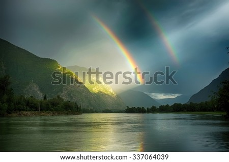 Deep filtered double rainbow over the lake. Amazing play of light after the rain in the mountains, Altai. Window in a heaven. Door in the paradise. Rainbow reflection in the water. - stock photo