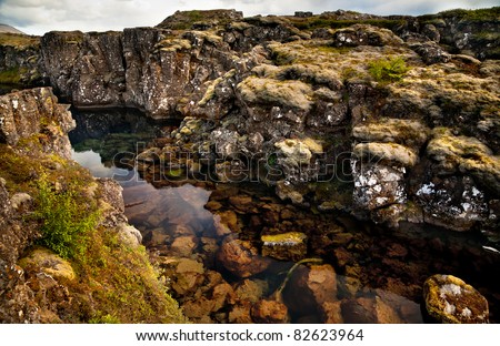 Deep fissure Flosagja with crystal clear cold water at Thingvellir National Park. The fissure in the earth's crust where the european and american continental plates drift apart. - stock photo