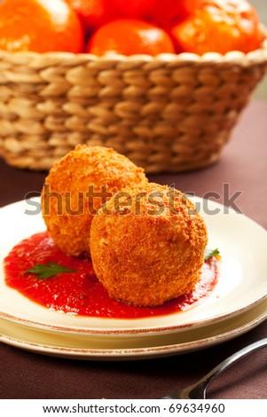 Deep fried balls of arborio rice stuffed with mozzarella cheese - stock photo