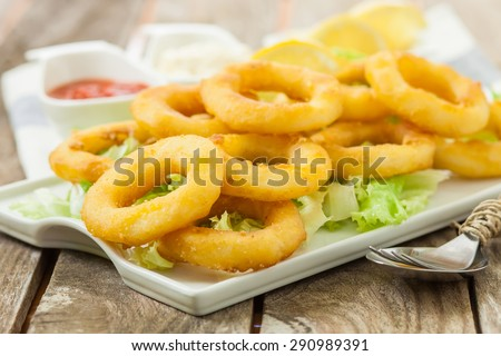 deep fried calamari with lemon and salad on white tray - stock photo