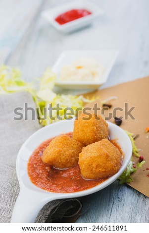 Deep fried cheese balls on a wooden table with souce - stock photo