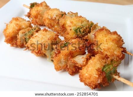 Deep fried chicken kushi sticks on plate. - stock photo