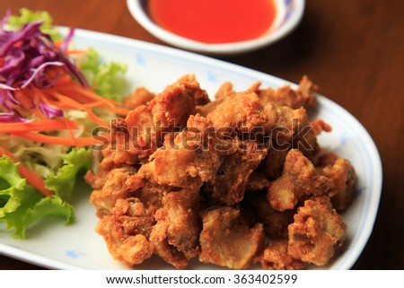 deep fried chicken tendons and sauce on white dish with wooden background