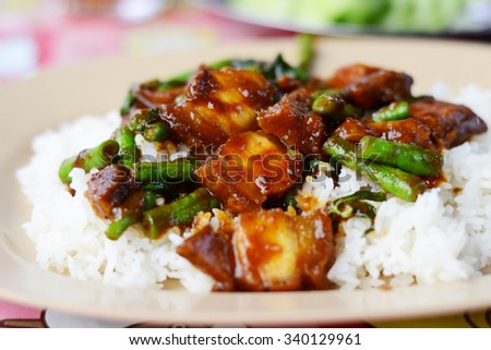 deep fried crispy pork with red curry top on rice