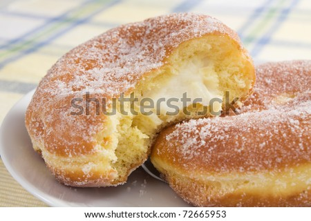 Deep-fried doughnuts (paczki) filled with cream cheese are eaten on Fat Tuesday before Lent. - stock photo