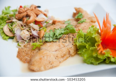 Deep fried fish serve with spicy salad and vegetables