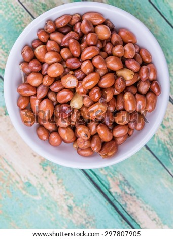 Deep fried peanuts in white bowl over rustic wooden background - stock photo