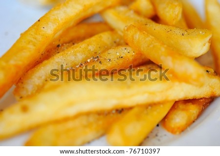 Deep fried potato sticks with sprinkled spices. - stock photo