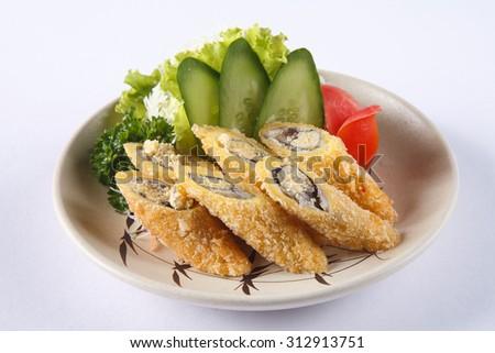 Deep fried Shishamo on ceramic dish isolated on white background. - stock photo