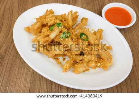 Deep fried squid calamari with spicy sriracha sauce served on wooden table - stock photo