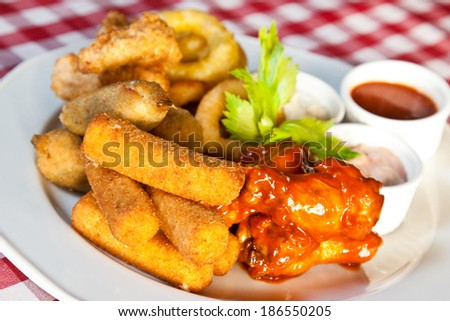 Deep-fried squid rings, mozzarella cheese sticks and chicken wings - stock photo