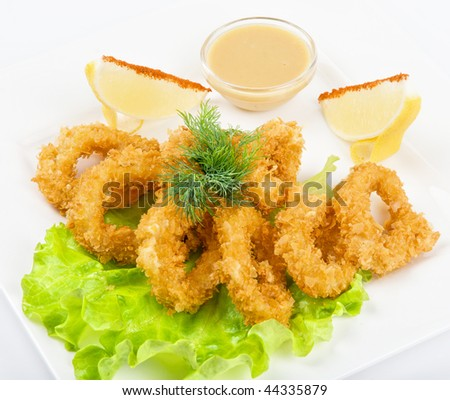 Deep-fried squid with salad leaves, sauce, green and lemon on a white background
