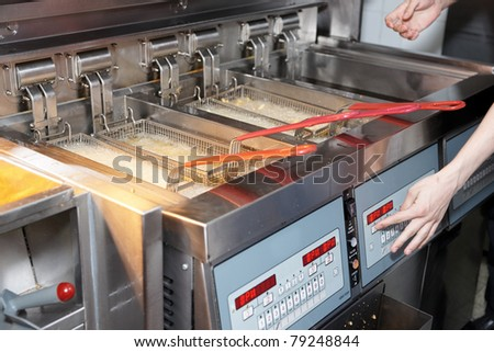 Deep fryer with boiling oil on restaurant kitchen - stock photo