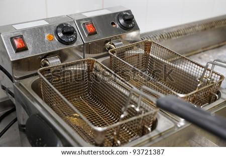 Deep fryer with oil on restaurant kitchen - stock photo