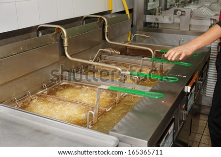 Deep fryers with boiling oil on fast food kitchen - stock photo