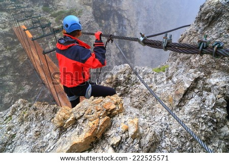"Deep gap crossed on wooden bridge by the climber of via ferrata ""Brigata Tridentina"", Sella massif, Dolomite Alps, Italy - stock photo"