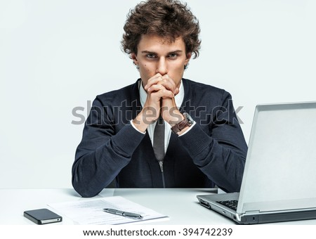 Deep in thought man. Businessman at the workplace working with computer on gray background. - stock photo