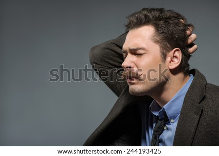 Deep in thoughts. Young nerd in retro suit touching his head while sitting against grey background - stock photo