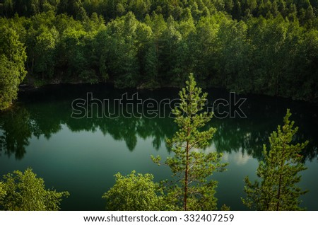deep lake of green color in the forest - stock photo