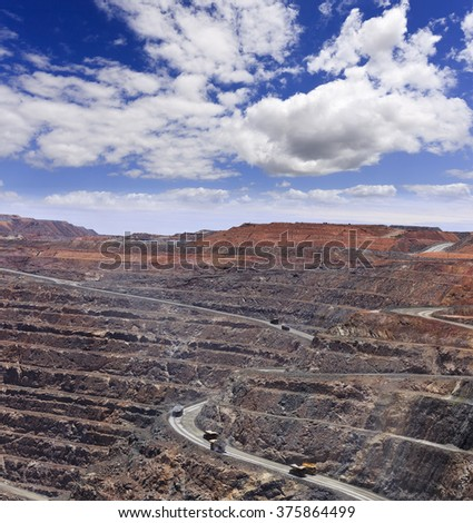 deep open gold mine - super pit, in Kalgoorlie Boulder, Western Australia. Layers of mine hole with huge trucks carrying loads of raw mineral ore. - stock photo