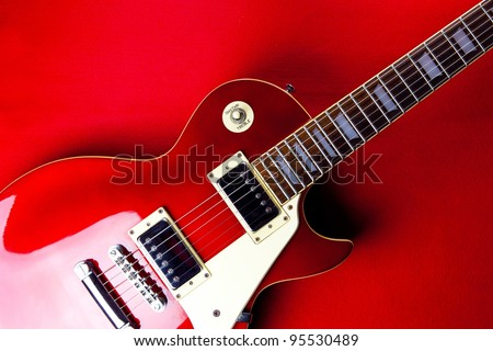 Deep red metallic vintage solid body electric guitar on deep red background. - stock photo