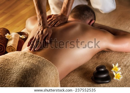 Deep tissue massage. Spa setup - stones, frangipani flowers and towels. - stock photo
