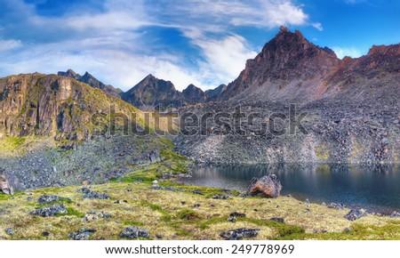 Deepest lake under the mountain peak. Eastern Sayan. Siberia - stock photo