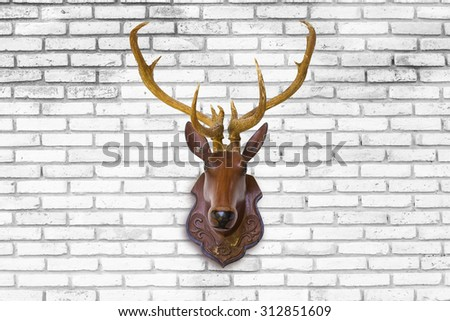 Deer head made of red wood on blurred white brick wall background. - stock photo