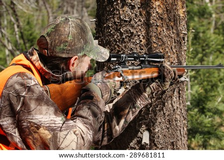 deer hunter aiming rifle - stock photo