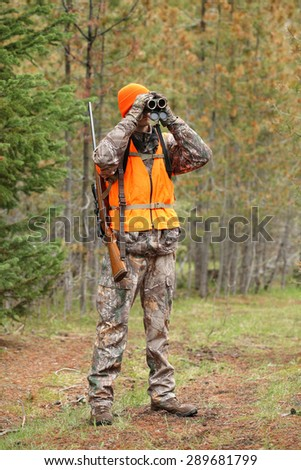 deer hunter using binoculars - stock photo