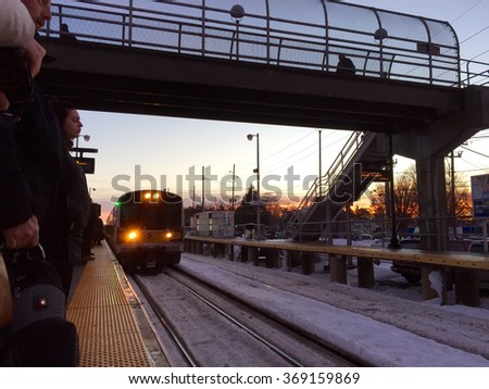 Deer Park, New York - January 26, 2016: Commuters on Long Island await an approaching LIRR train on the platform returning to work after Blizzard Jonas shut down parts of the NY area.  - stock photo