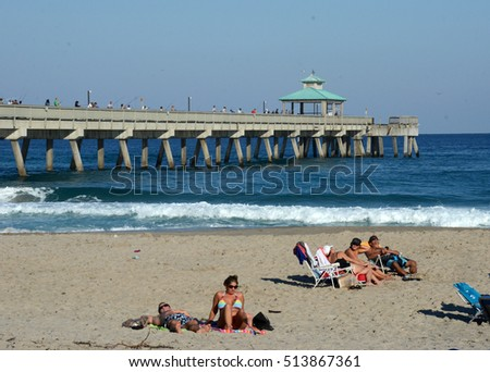 DEERFIELD BEACH - NOVEMBER 24: Tourists and locals enjoy a sunny day on the beach in Deerfield Beach Florida on November 24, 2012.