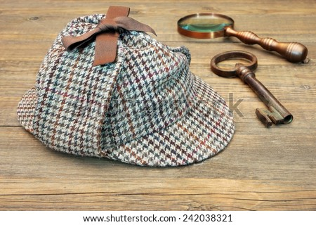 Deerstalker Hat, Retro Magnifying Glass and Large Old Key on Wooden Table - stock photo
