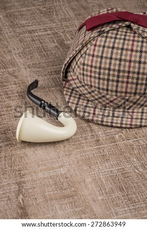 Deerstalker or Sherlock Hat and Tobacco pipe on Old Wooden table. - stock photo