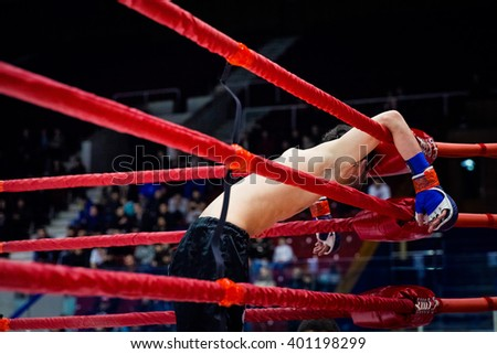 defeat MMA fighter on ropes of ring after fight - stock photo