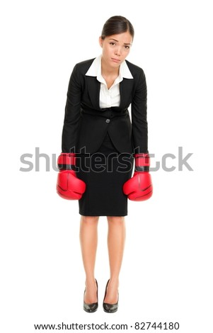 Defeated loser woman - business concept with businesswoman wearing boxing gloves standing in full body looking hopeless. Young Asian / Caucasian female professional isolated on white background. - stock photo